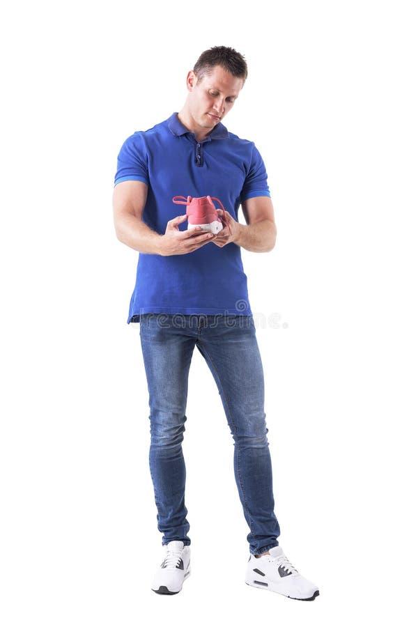 Interessierter männlicher Käufer, der bequeme Turnschuhe hält und überprüft stockbilder