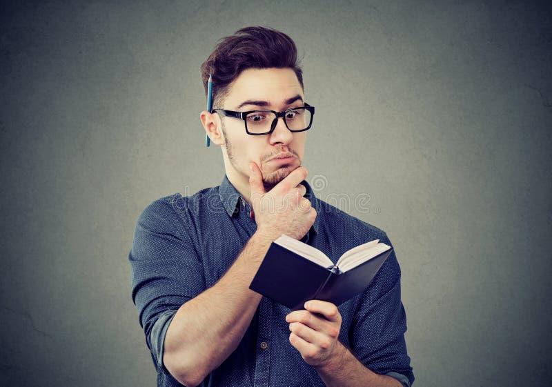 Interessierter Mann, der einen Notizblock liest stockfotos