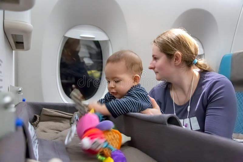 Interest to special baby bassinet during the flight. First flight of infant girl. mother holds baby in her arms in plane.  royalty free stock photos