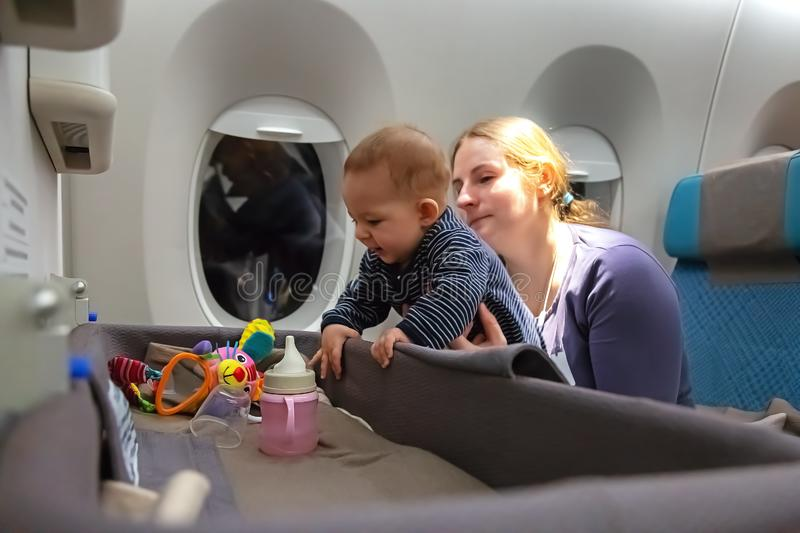 Interest to special baby bassinet during the flight.  Infant plays on mother hands at the airplane.  Travelling with mom. Infant plays on mother hands at the stock image