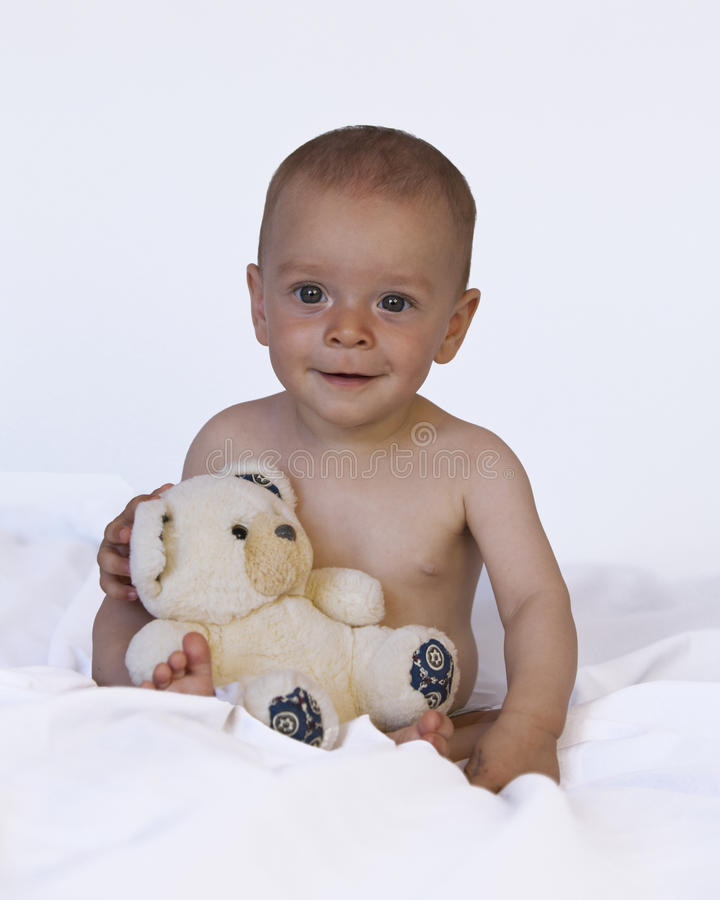 Interested baby playing with teddy bear royalty free stock photos