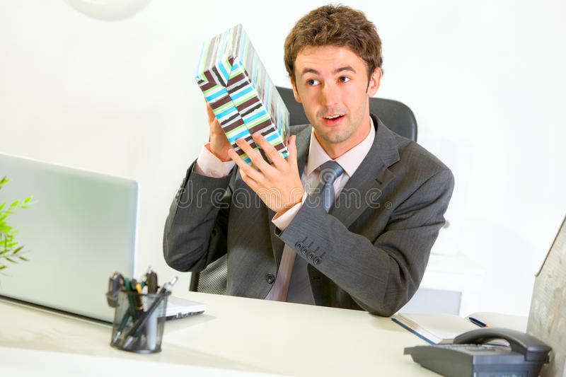Interested businessman shaking present box. Interested modern businessman shaking present box trying to guess what's inside royalty free stock photos