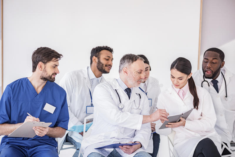 Interested doctors watching at notebook in hospital. Calm old physician correcting mistakes in memorandum pad of young smiling therapeutic before meeting while stock photo