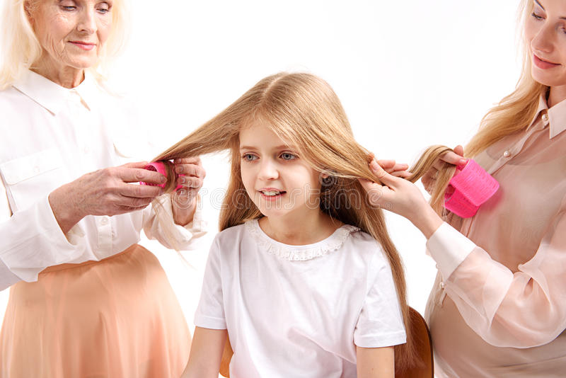 Interested glance of young female person. Curious girl is sitting among her mother and granny. They using hair curler stock photo