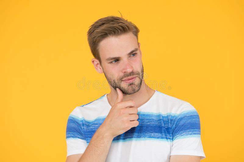 Interested in my beard and my barber. Thoughtful guy touching unshaven chin hair before going to barber shop. Bearded. Man thinking of visiting barber. Barber stock photography