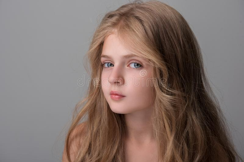Pretty child is standing wistfully. Interested small lovely girl with long hair is looking at camera with kindness in eyes. Isolated background. Copy space stock photo