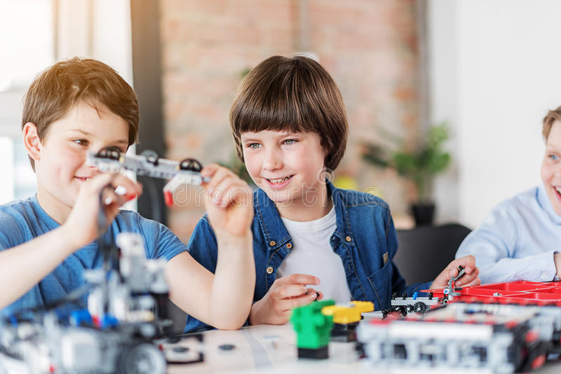 Interested smiling children making technical toy royalty free stock photography