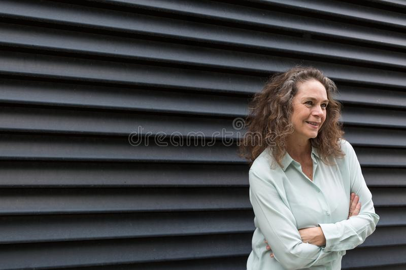 Interested woman leaning forwards watching. Interested attractive mature woman leaning forwards watching with folded arms and an absorbed expression on front of stock photos