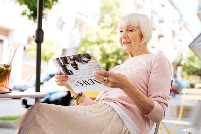 Glad senior woman reading newspaper royalty free stock photos