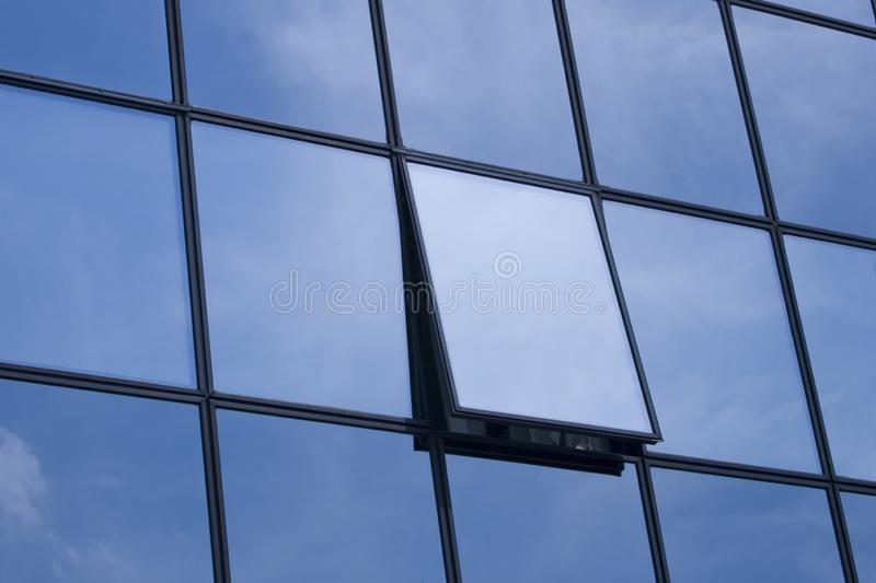 Interesting background with an urban skyscraper with open windows in which the sky is reflected. Beautiful interesting background with an urban skyscraper with royalty free stock images
