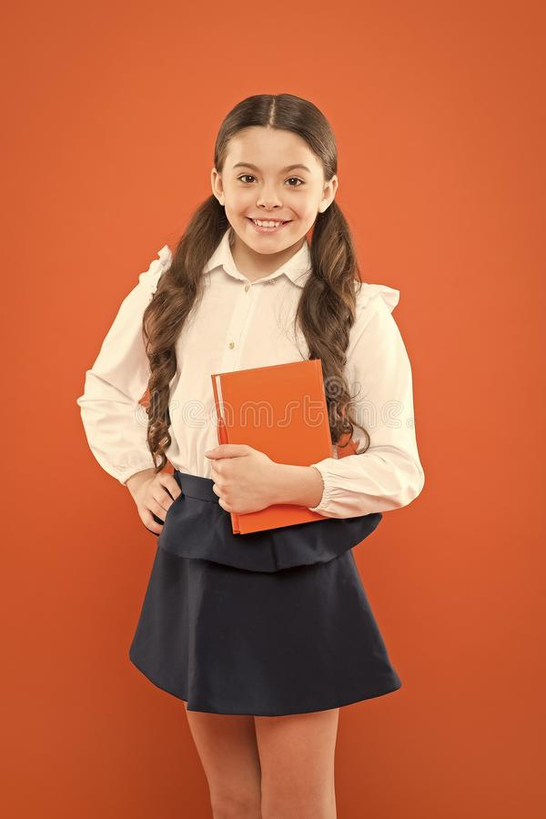 Interesting book for children. small girl in school uniform. get information form book. schoolgirl writing notes on royalty free stock images
