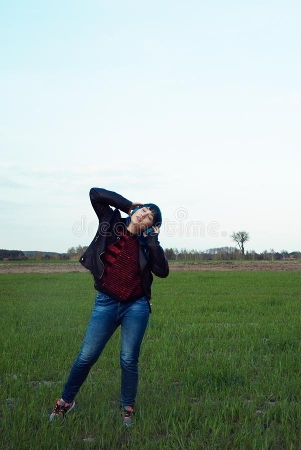 An interesting girl in blue hair, listens to music and dances in the field. An interesting girl in blue hair, listens to music in blue, big headscarfs and stock photography