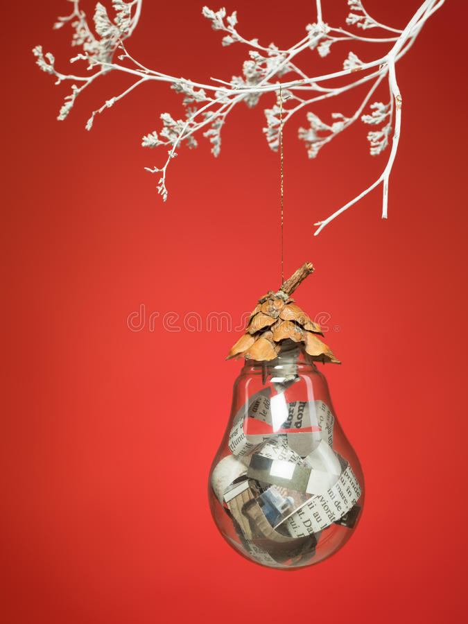 Interesting idea for christmas decorations. Closeup of handmade christmas globe made out of recycled materials hanging by a white painted interesting branch on royalty free stock image