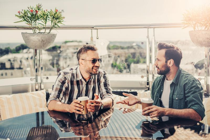 Two bearded men having conversation at outdoor cafe. Interesting meeting. Male friends sitting at the table and communicating. They looking at each other and royalty free stock photography
