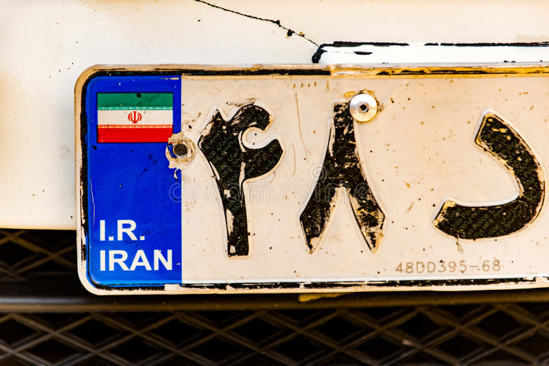 Interesting old Teheran license plate. Close up of shabby numberplate with Iranian coloured flag royalty free stock photography