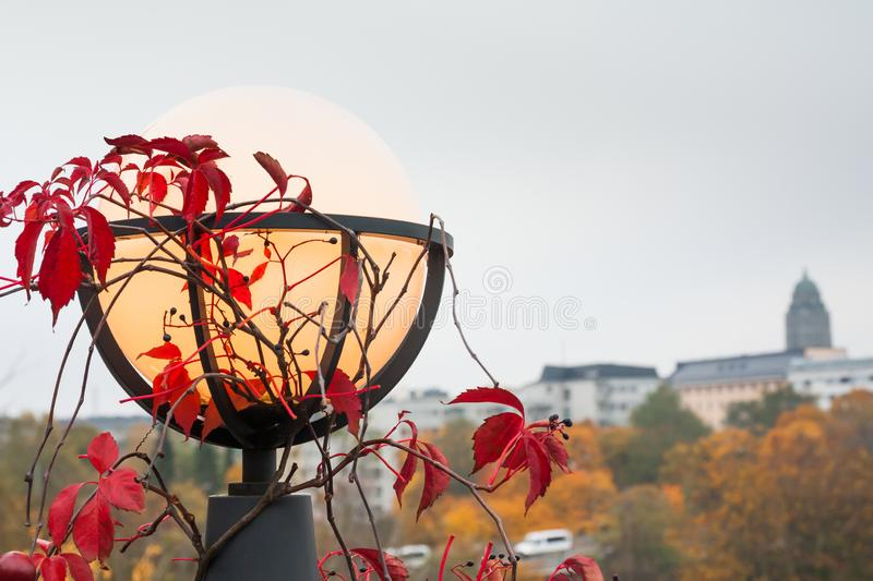 Interesting outdoor lantern used for decor and night lighting with red leaves at autumn. Interesting outdoor lighting lamps used for decor and night lighting royalty free stock photography