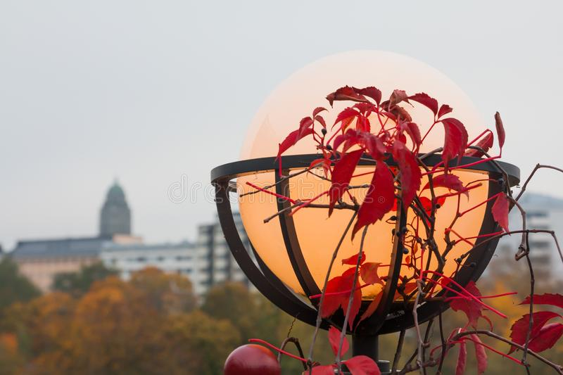 Interesting outdoor lantern used for decor and night lighting with red leaves at autumn. Interesting outdoor lighting lamps used for decor and night lighting royalty free stock image