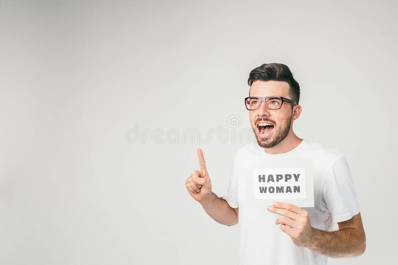 Interesting picture of a young man stading with a inscripition Happy Woman. This man has a thought for that and want to stock image