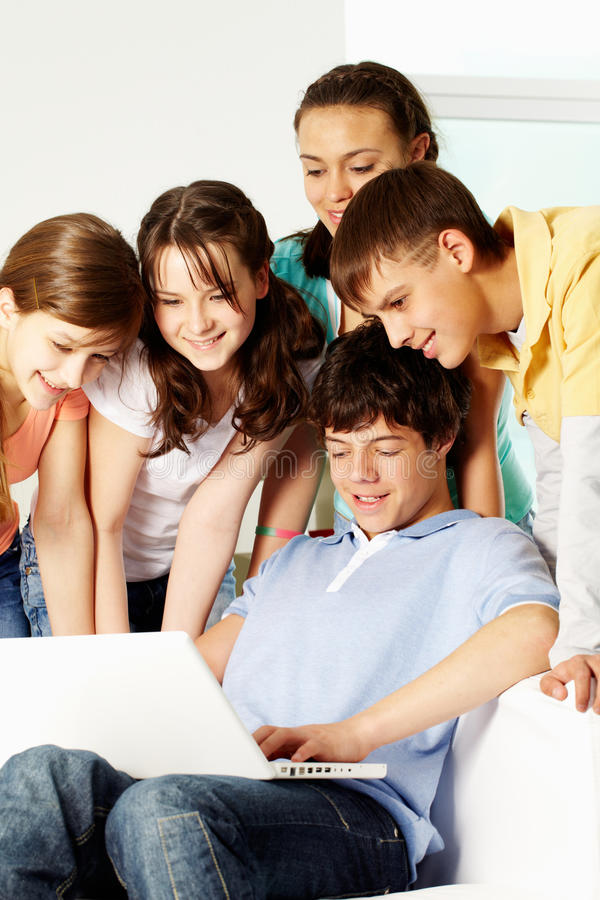 Interesting presentation. A boy showing something on a laptop to his friends stock photography
