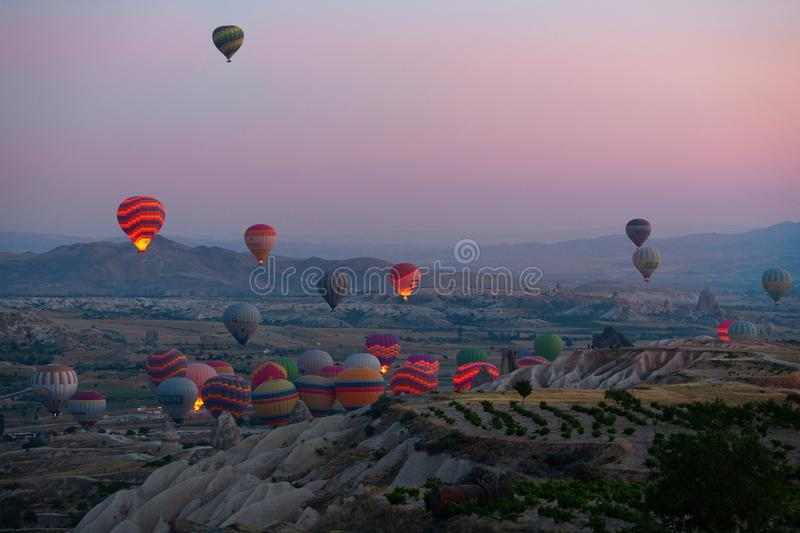 Interesting rocky terrain and a lot of airy multicolored balls in the air. Turkey. Cappadocia. stock image