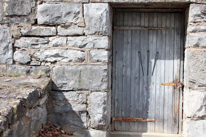 Interesting stone building with carved wood door. Interesting stone wall and building with old weathered door,rusty metal hinges and strange carvings on the stock photo