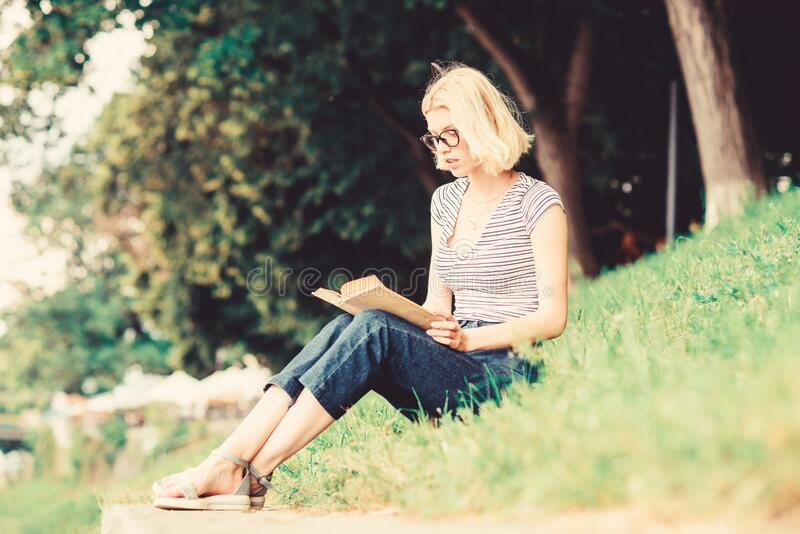 Interesting story. Relax and get new information. student girl with book outdoor. woman in park reading book. inspired. By novel author. reading is my hobby stock image