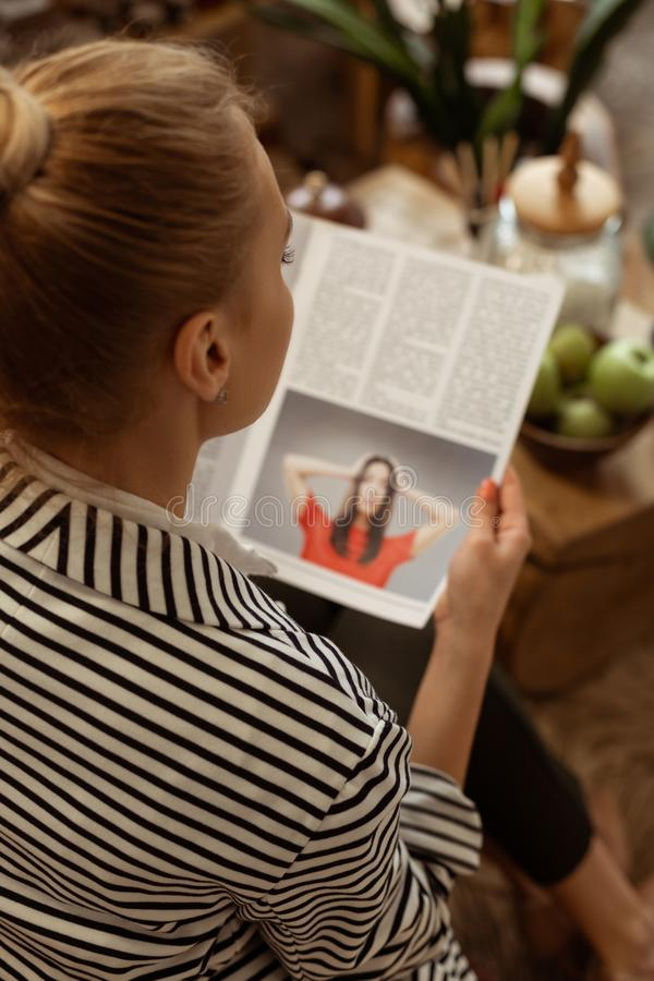 Diligent calm woman being busy with reading glance pages royalty free stock photo