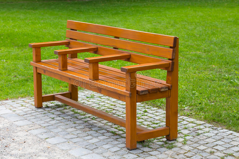 Interesting unusual wooden park bench at a park. Divided on three part stock photo