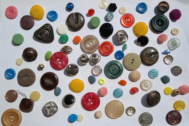 Interesting variety of many bright colorful variety of round buttons, different textures, diameter, on a white background. Interesting of many bright colorful stock photo