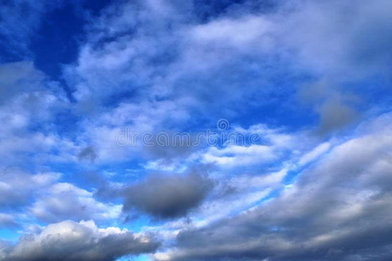 Interesting white and dark mixed cloud formations on a blue sky in spring stock photos