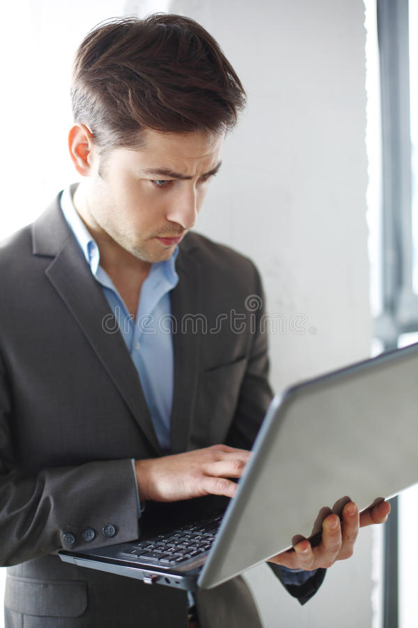 Interests. Man in suit working with a computer stock photography