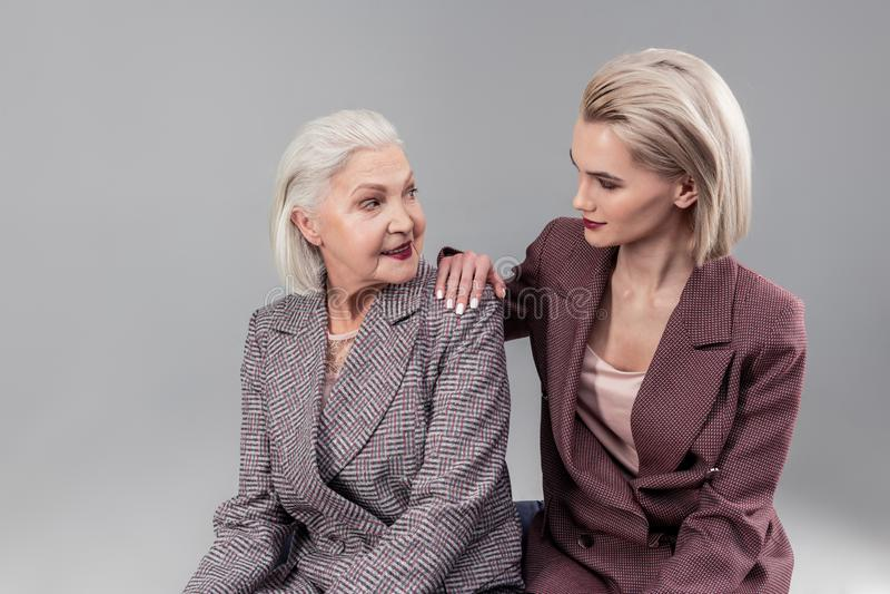 Interesująca blondynki kobieta stawia jeden rękę na ramieniu zdziwiona matka fotografia stock