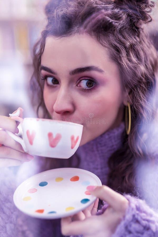 Interesująca ciemnowłosa kobieta z dużym brązem przygląda się popijanie herbaty fotografia royalty free