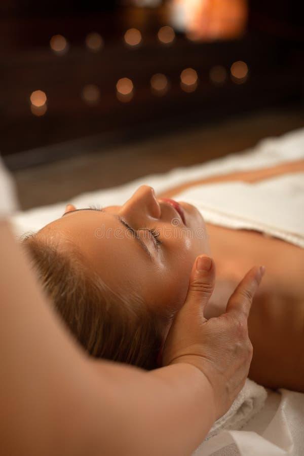 Interesująca doskonała dama z wiązanym włosianym dosypianiem podczas twarz masażu obrazy stock