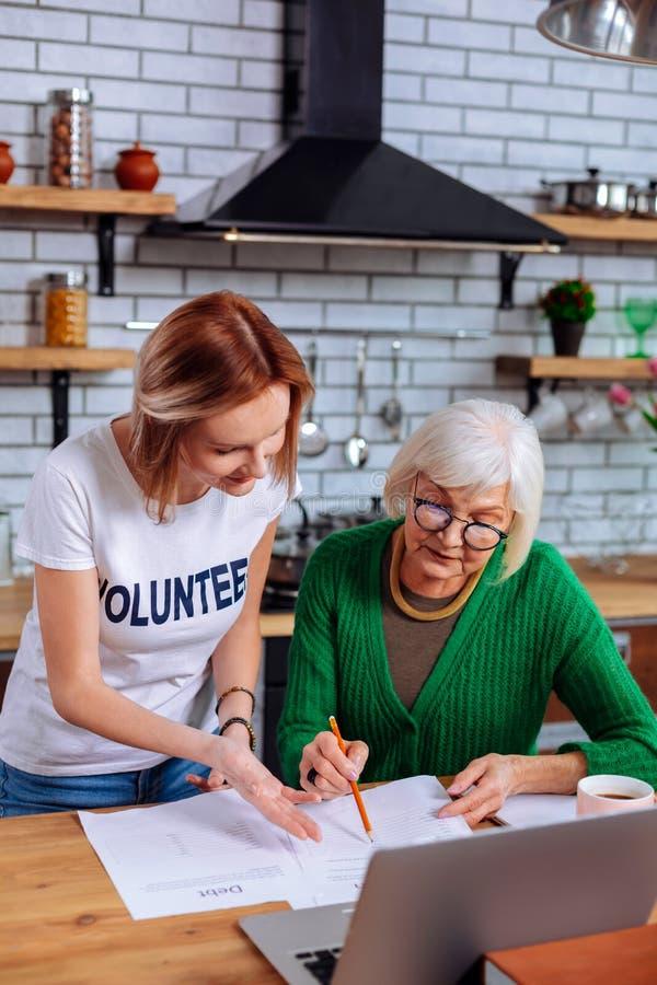 Interesująca starsza kobieta pyta dorosły damy dla pomagać z papierami zdjęcie stock