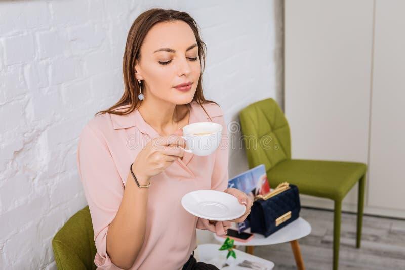 Interesujący elegancki bizneswoman cieszy się filiżankę świeża smakowita kawa obraz stock
