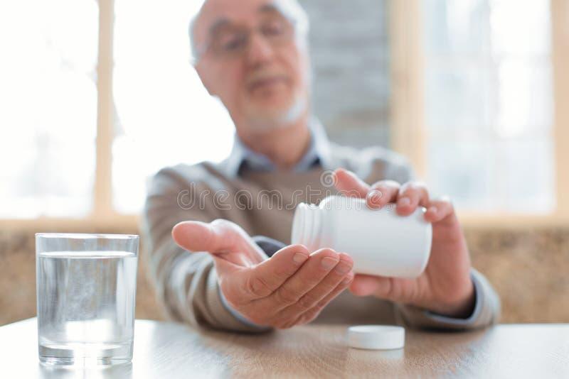 Interesujący starszy mężczyzna spożywa lekarstwo zdjęcie royalty free