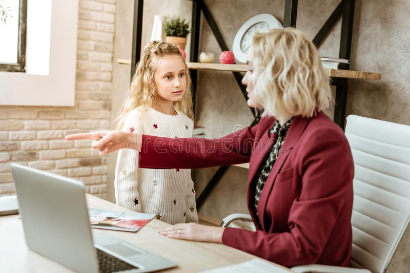 Angry strict mother pointing on exit while her little daughter disturbing her royalty free stock photos