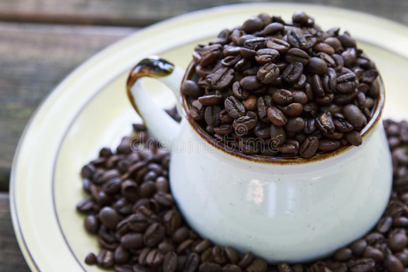 Interi chicchi di caffè in una tazza immagine stock