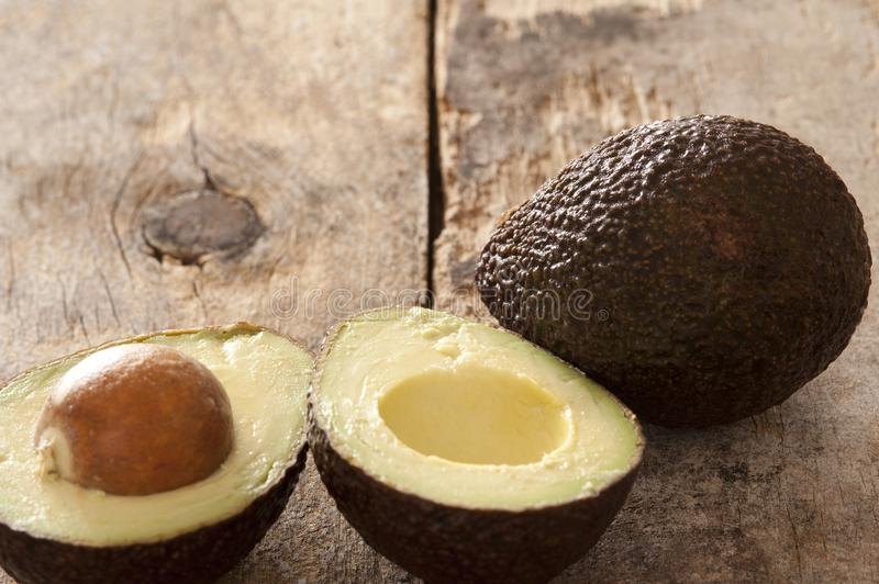 Interi e avocado maturi divisi in due saporiti immagine stock