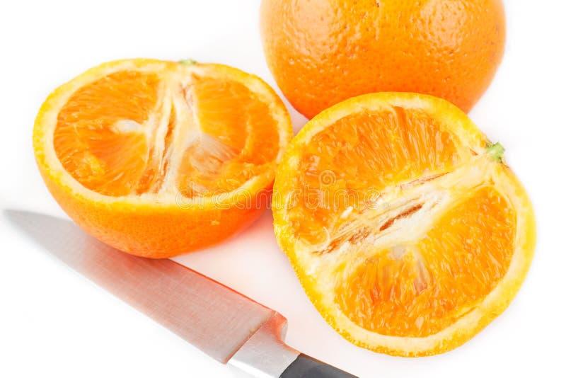 Interi ed aranci affettati fotografia stock