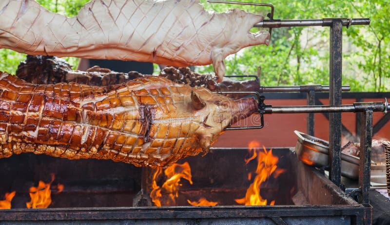 Interi maiali su uno sputo su un barbecue fotografia stock libera da diritti