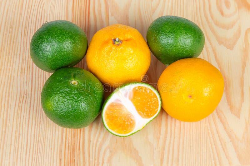 Interi mandarini verdi ed arancio maturi e mezzo mandarino verde fotografia stock libera da diritti