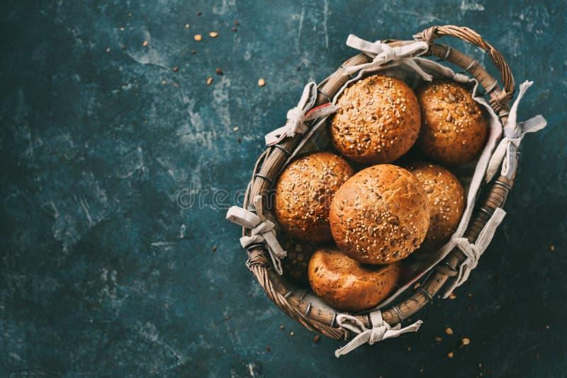 Interi panini del grano in un canestro per la prima colazione o gli hamburger fotografie stock libere da diritti