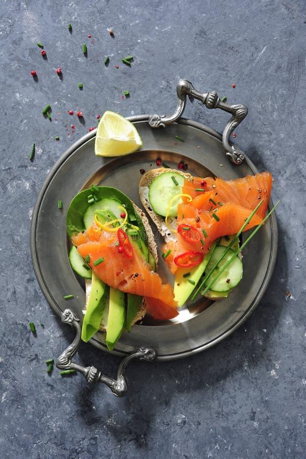 Interi panini del pane del grano con il cetriolo, le foglie degli spinaci, l'avocado ed il salmone affumicato freschi fotografie stock