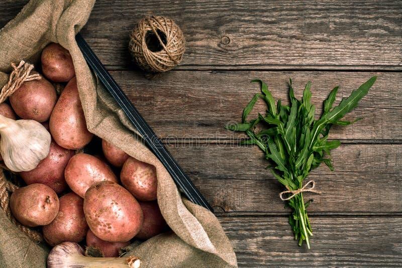 Interi patate, aglio e ruccola organici lavati crudi su tela di sacco sopra il vecchio fondo di legno della plancia Vista superio fotografia stock libera da diritti