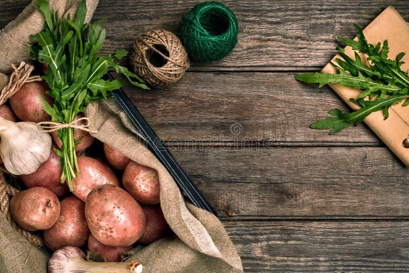 Interi patate, aglio e ruccola organici lavati crudi su tela di sacco sopra il vecchio fondo di legno della plancia Vista superio fotografie stock