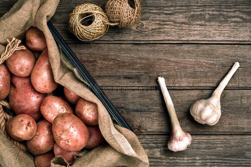 Interi patate ed aglio organici lavati crudi su tela di sacco sopra il vecchio fondo di legno della plancia Vista superiore con s immagini stock