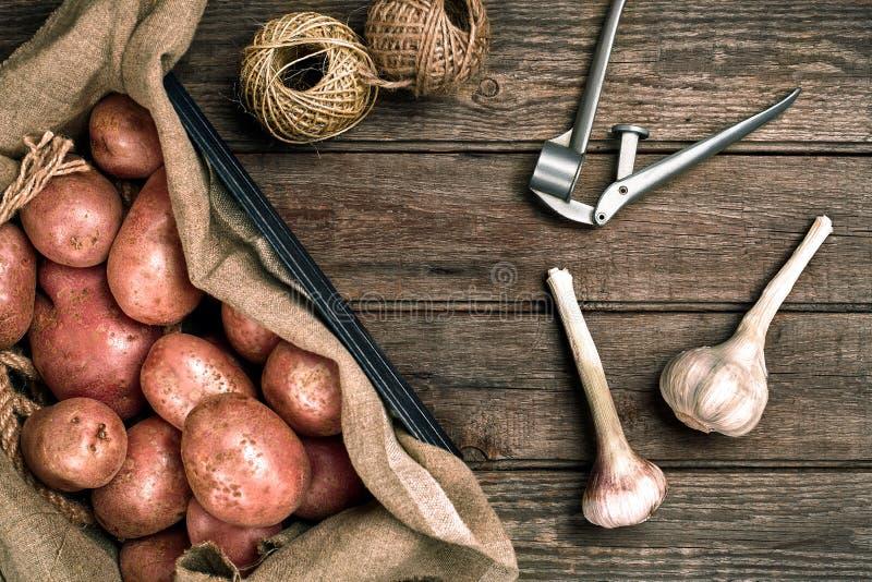 Interi patate ed aglio organici lavati crudi su tela di sacco sopra il vecchio fondo di legno della plancia Vista superiore con s immagine stock libera da diritti