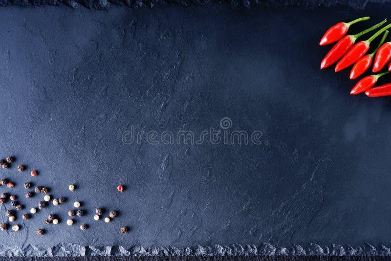 Interi pepe nero e peperoncino sul piatto di pietra fotografie stock